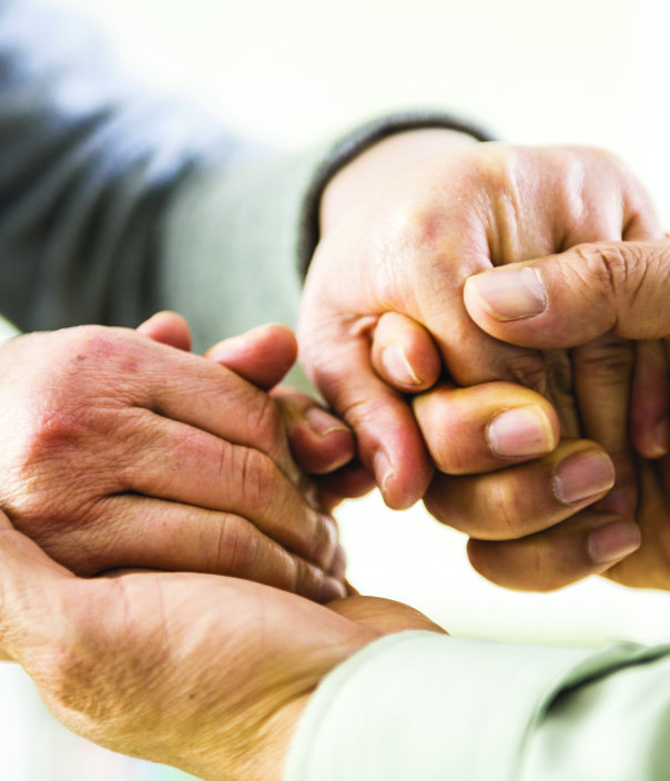 Two sets of hands grasping each other