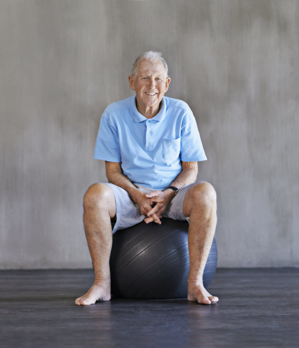 Shot of an elderly man using weights while sitting on a swiss ball