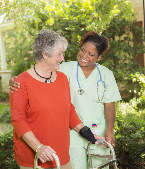 A senior adult woman patient wearing a red shirt and using a walker smiles as she visits with her medical professional outdoors. The pair are on the grounds of the nursing home or assisted living facility. They are walking along a sidewalk with many green trees in the background. Summer or spring.