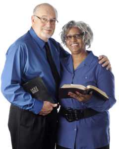 A mixed race senior couple happily holding their Bibles. On a white background.