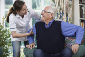 Care Worker Helping Senior Man To Get Up