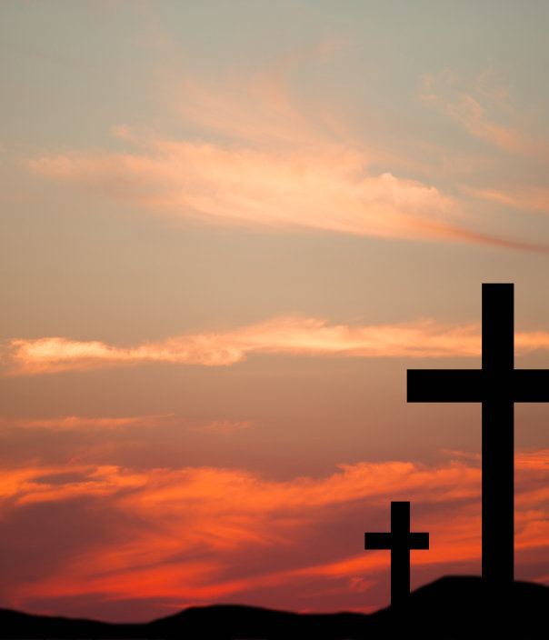 Easter. The crucifixion. Three wooden crosses in silhouette stand silently on a hill at sunset. The dramatic sky is beautiful in its blue and orange colors. Christianity, religious themes.