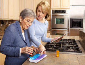 An elderly woman adding pills to her organizer. A caregiver or family member is holding a pen and pad of notepaper while helping her. This organizer has compartments for both morning pills and evening pills each day.