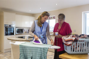 Care worker making a home visit. Female carer is ironing in the kitchen to help an elderly woman. The elderly woman is standing behind her chatting.