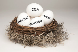 White eggs in a brown nest labelled with IRA, Pension, 401k and House representing a typical nest egg.