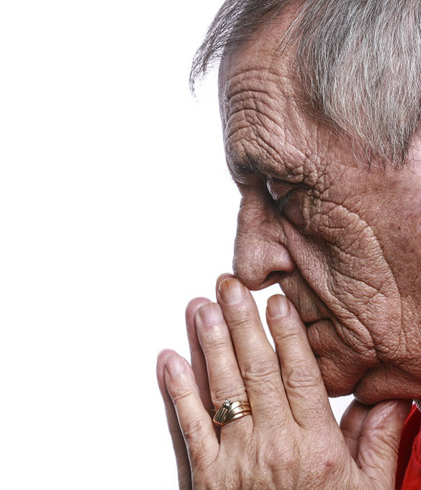 Shot on white background, profile of a 70 year old man praying with his eyes closed.