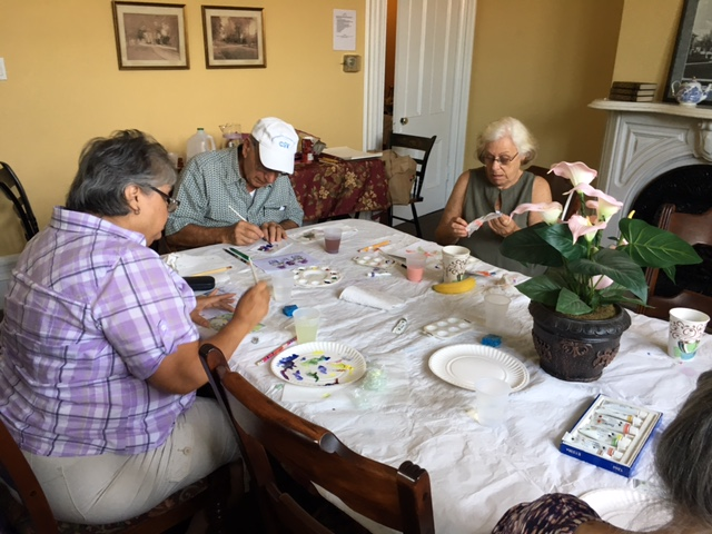 Four seniors immerse themselves in a group watercolor class.